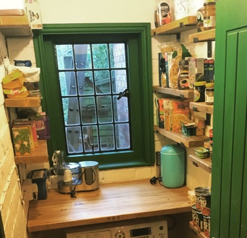 Larder with narrow wooden shelves and wooden counter